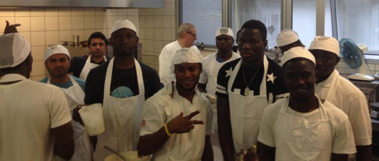 Richiedenti asilo preparano i pasti durante il laboratorio di cucina